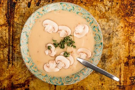 Чаша из свежего домашнего грибного супа на потрепанной духовке или выпечке
