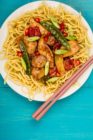 Chinese Style Chicken and Cashew Nuts Stir Fry Meal On A Blue Wooden Background Stock Photo