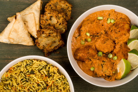 Indian Style Vegetable Kofta Curry Meal On A Green Wooden Background With Pillau Rice and Samosas