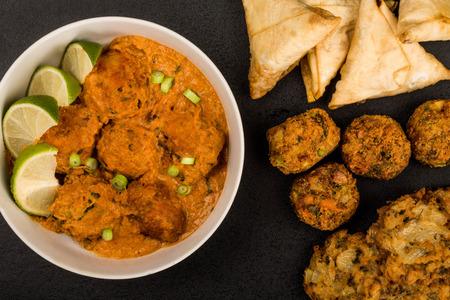 Indian Style Vegetable Kofta Curry Meal On A Black Background With Samosas Onion Bhaji and Pakoras