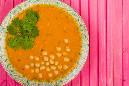 Bowl of Carrot and Coriander Soup Against A Pink Wooden Background Stock Photo
