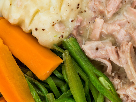Pulled Ham in a Mustard Sauce With Beans and Carrots Against a Blue Wooden Background