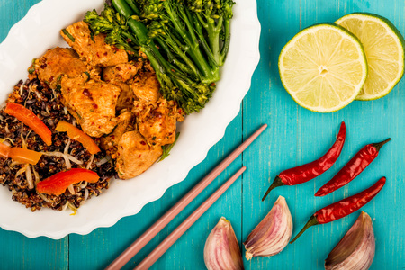 Soy Ginger and Lime Chicken With Red Quinoa and Vegetables Against A Blue Backgorund