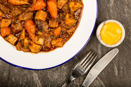 Beef and Red wine Casserole With Roast Potatoes Carrots and Mushrooms Against a Black Background Stock Photo