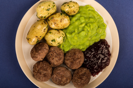 Norwegian or Sweedish Meatballs With Mushy Peas Boiled Potatoes and Cranberry Sauce Against A Purple or Blue Backgound Stock Photo
