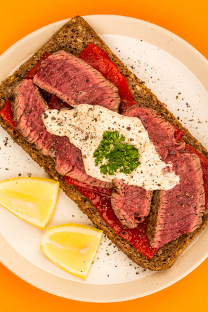 Rare Cooked Beef Steak And Red Pepper Open Face Sandwich With Horseradish Sauce Against An Orange Background Stock Photo