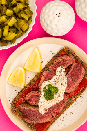 Rare Cooked Beef Steak And Red Pepper Open Face Sandwich With Horseradish Sauce Against A Pink Background