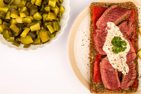 Rare Cooked Beef Steak And Red Pepper Open Face Sandwich With Horseradish Sauce Against A White Background