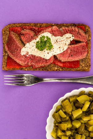 Rare Cooked Beef Steak And Red Pepper Open Face Sandwich With Horseradish Sauce Against A Purple Background Stock Photo