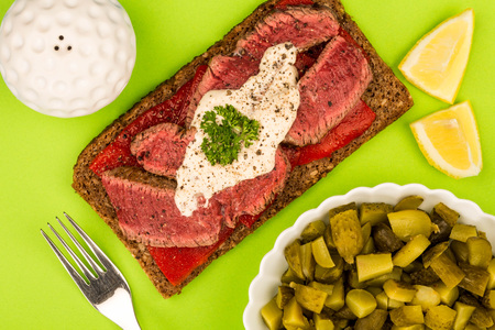 Rare Cooked Beef Steak And Red Pepper Open Face Sandwich With Horseradish Sauce Against A Green Background Stock Photo