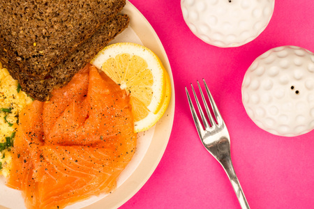 Smoked Salmon and Scrambled Eggs With Rye Bread and Lemon Scandinavian Style Breakfast Against A Pink Background Stock Photo
