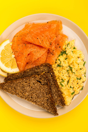 Smoked Salmon and Scrambled Eggs With Rye Bread and Lemon Scandinavian Style Breakfast Against A Yellow Background Stock Photo