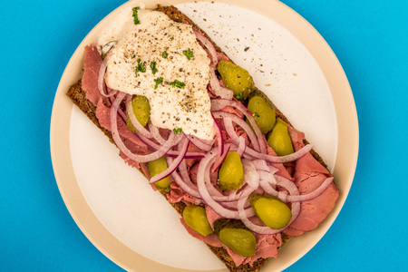 Roast Beef Open Faced Sandwich With Sliced Onions Gherkins and Horseradish Sauce On Rye Bread Against A Blue Background