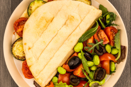 Veghetarian Style Courgette and Cherry Tomato Flatbread With A Fresh Mixed Salad Against A Dark Wooden Table Top Stock Photo