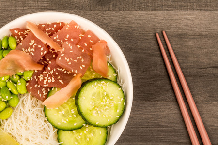Hawaiian Tuna Fish Poke bowl With Noodles and Edamame Beans On A Dark Wooden Kitchen Table Background