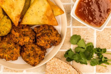 Indian Food Style Snacks Vegetarian Tikka Vegetarian Samosa Onion Bhaji With Chapati Flat Bread On A Tiled Kitchen Table Top Stock Photo