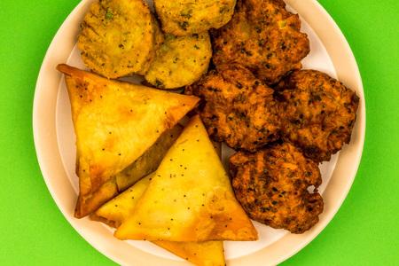 Indian Food Style Snacks Vegetarian Tikka Vegetarian Samosa Onion Bhaji Against A Green Background