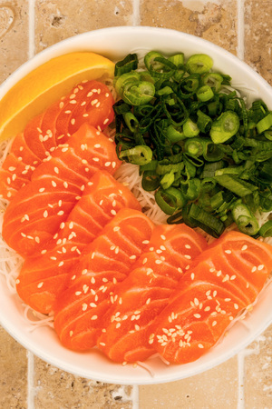 Hawaiian Poke bowl Of Salmon Sashimi With Rice Noodles And Spring Onions On A Tiled Kitchen Table Top Stock Photo