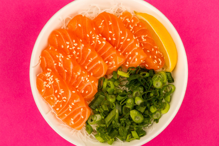 Hawaiian Poke bowl Of Salmon Sashimi With Rice Noodles And Spring Onions Against A Pink Background