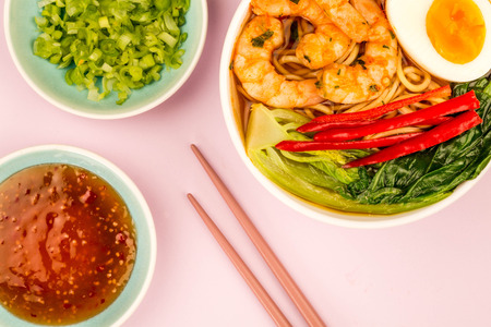 Japanese Style Prawn And Noodle Ramen Soup With Pak Choi And Chillies Against A Pink Background