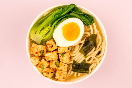 Japanese Style Vegetarian Tofu Noodle Ramen Soup or Broth Against A Pale Pink Background