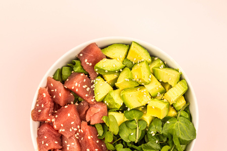 Hawaiian Style Tuna And Avocado Sashimi Poke Food Bowl Against A Light Pink Background