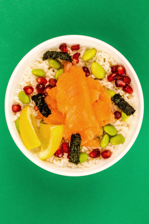 Healthy Hawaiian Style Poke Bowl Of Smoked Salmon With Rice Edamame beans Seaweed and Pomegranate Seeds Against A Green Background