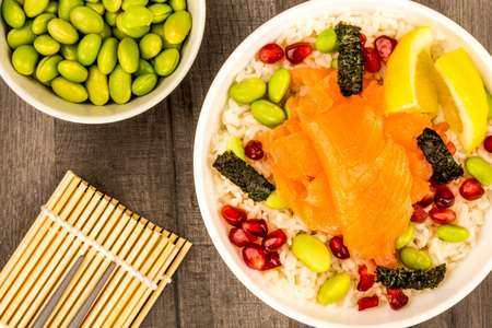 Healthy Hawaiian Style Poke Bowl Of Smoked Salmon With Rice Edamame beans Seaweed and Pomegranate Seeds On A Dark Wooden Table Top Stock Photo