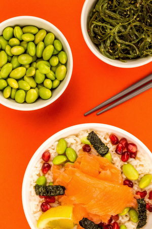 Healthy Hawaiian Style Poke Bowl Of Smoked Salmon With Rice Edamame beans Seaweed and Pomegranate Seeds Against A Red Background