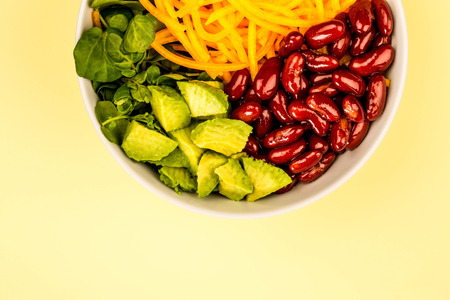 Vegan or Vegetarian Food Bowl With Kidney Beans Carrots Avocado and Watercress Salad Against A Lemon or Pale Yellow Background