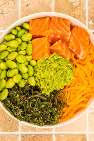 Hawaiian Style Raw Salmon Sashimi Poke Bowl With Edamame Beans And Seaweed On A Tiled Kitchen Table Top