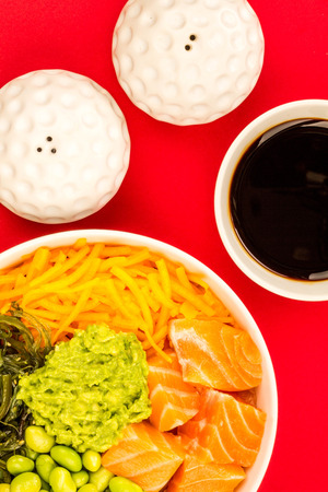 Hawaiian Style Raw Salmon Sashimi Poke Bowl With Edamame Beans And Seaweed Against A Red Background