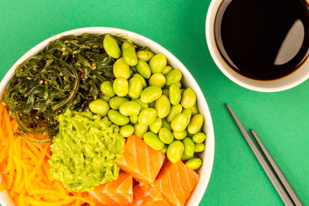 Hawaiian Style Raw Salmon Sashimi Poke Bowl With Edamame Beans And Seaweed Against A Green Background
