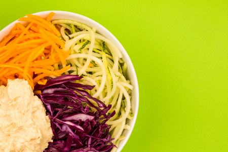 Vegan or Vegetarian Salad Bowl With Red Cabbage Courgettes Carrots And Hummus Again A Green Backgorund