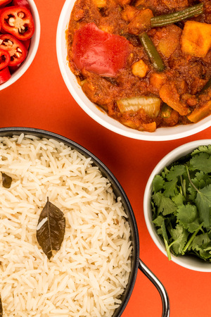 Indian Style Vegetarian Masala Curry Against A Red Background With Basmati Rice Red Chillies and Coriander