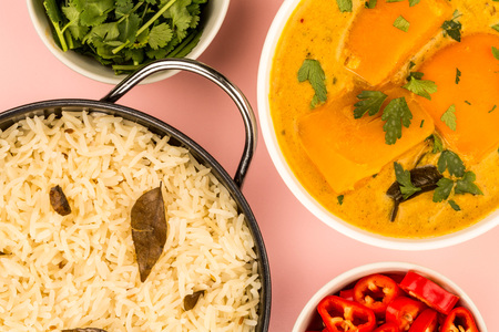Indian Style Butternut Squash Curry Against A Pink Background With Red Chillies And Coriander