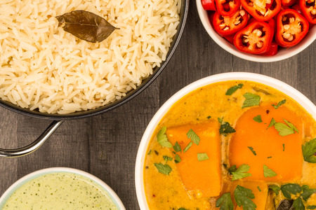 Indian Style Butternut Squash Curry Against A Dark Wooden Table Top Background With Red Chillies Dipping Sauce And Basmati Rice Stock Photo