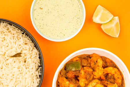 Spicy Indian Style King Prawn Bhuna Curry Against An Orange Background With Basmati Rice A Dipping Sauce And Limes