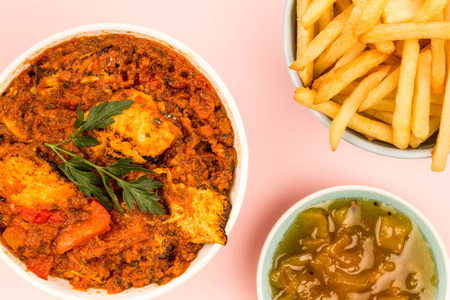Indian Style Chicken Balti Curry Against A Pink Background With Mango Chutney And Chips Or Fries