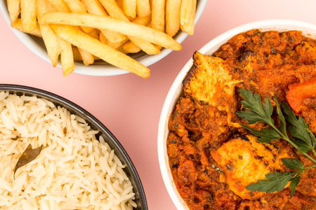 Indian Style Chicken Balti Curry Against A Pink Background With Basmati Rice And Chips or French Fries Stock Photo