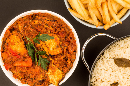 Indian Style Chicken Balti Curry Against A Black Background With Basmati Rice and Chips French Fries Or Frites