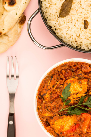Indian Style Chicken Balti Curry Against A Pink Background With Basmati Rice And Naan Flatbread Stock Photo
