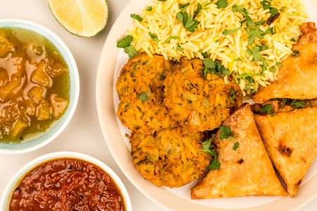 Onion Bhajis And Samosas With Pilau Rice Against A Grey Background With Mango Chutney A Dipping Sauce And Fresh Lime