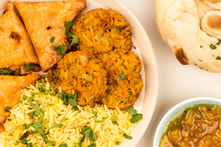 Onion Bhajis And Samosas With Pilau Rice Against A Grey Background With Naan Bread And Mango Chutney