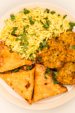 Onion Bhajis And Samosas With Pilau Rice Against A Grey Background
