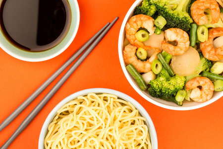 Chinese Style King Prawn With Ginger Broccoli And Spring Onions Against A Red Background Imagens