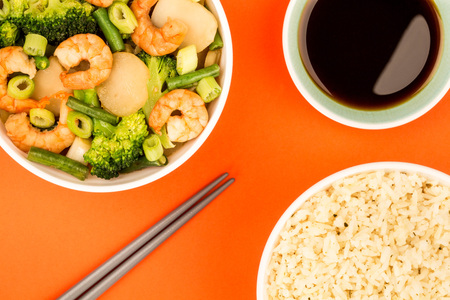 Chinese Style King Prawn With Ginger Broccoli And Spring Onions Against A Red Background Banco de Imagens
