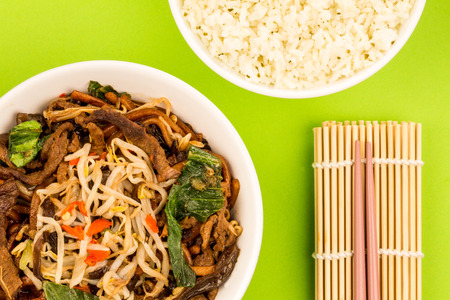 Chinese Style Wok Fried Shanghai Beef Noodles Against A Green Background