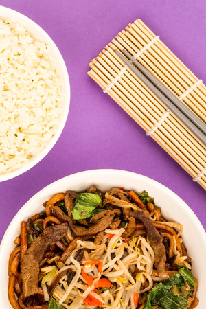 Chinese Style Wok Fried Shanghai Beef Noodles Against A Purple Background Stock Photo