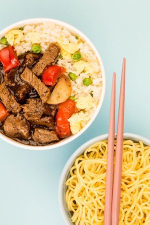 Chinese Style Beef In Black Bean Sauce With Fried Rice Against A Blue Background